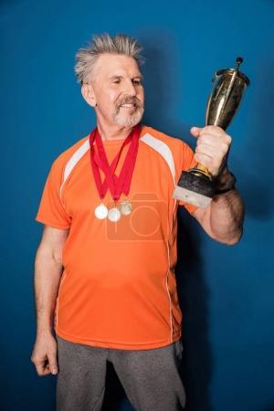 Photo pour Sportif mature souriant avec médailles tenant coupe trophée isolé sur bleu - image libre de droit