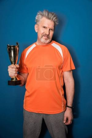 Senior sportsman with trophy