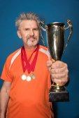 Senior sportsman with trophy