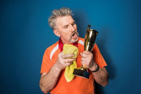 Photo for Bearded mature sportsman cleaning trophy cup isolated on blue - Royalty Free Image