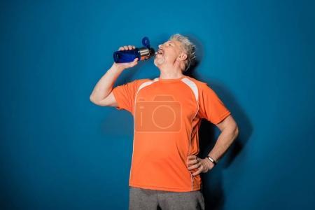 Photo pour Homme mûr sportif buvant de l'eau de bouteille de sport isolé sur bleu - image libre de droit