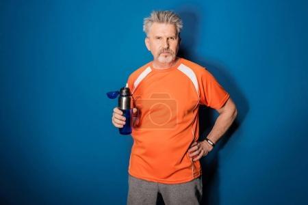 Photo pour Sportif mature confiant tenant une bouteille d'eau et regardant la caméra - image libre de droit