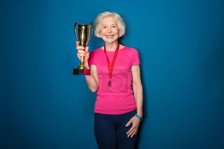 Photo pour Happy senior sportswoman holding trophy isolated on blue - image libre de droit