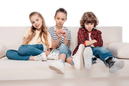 Photo pour Des amis mignons assis sur le canapé et ne parlent pas entre eux - image libre de droit