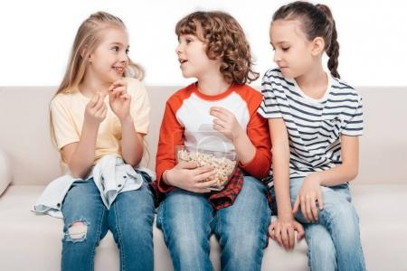 Cute children on couch with popcorn