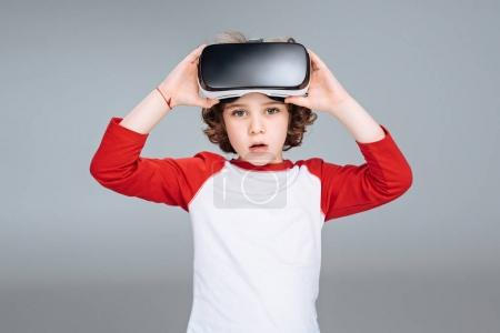 Photo for Little boy using virtual reality headset isolated on gray - Royalty Free Image