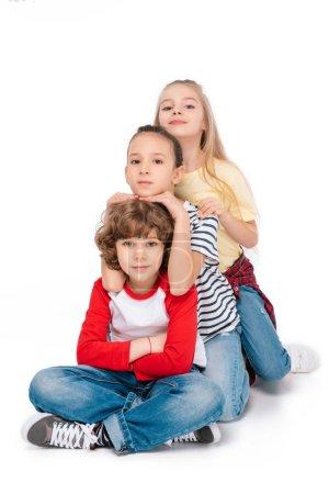 Photo pour Enfants joyeux assis sur le sol et riant isolé sur blanc - image libre de droit