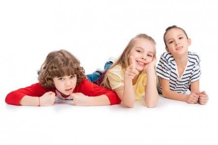 Photo pour Enfants gais couchés sur le sol et amusez-vous isolé sur blanc - image libre de droit