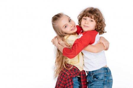 Photo pour Jeune garçon et fille embrasser et avoir du plaisir isolé sur blanc - image libre de droit