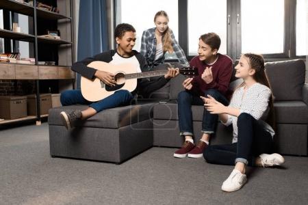 Photo pour Afro-américain garçon jouant de la guitare acoustique alors que ses amis l'écoute à la maison, adolescents jouant le concept de guitare - image libre de droit