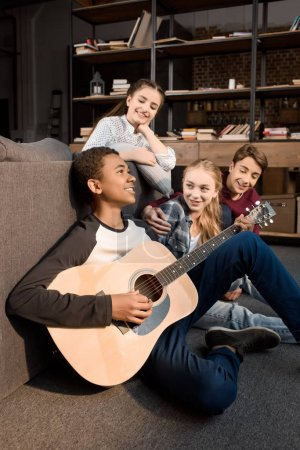 Teenagers playing acustic guitar