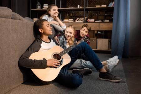 Photo pour Afro-américain garçon jouer de la guitare acoustique tandis que ses amis à l'écoute à la maison, adolescents jouant concept de guitare - image libre de droit