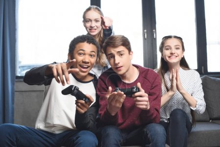 Multicultural teenagers with joysticks