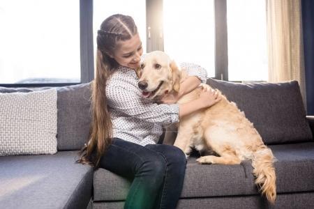Photo pour Adolescent fille étreinte golden retriever chien sur canapé à la maison - image libre de droit