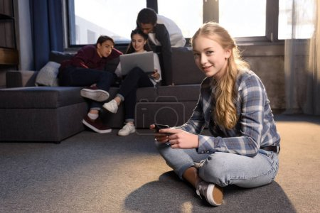 Photo for Smiling teenage girl sitting on floor and using smartphone with friends using laptop behind - Royalty Free Image