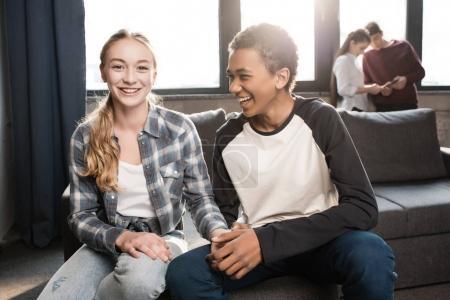 Foto de Feliz pareja de adolescentes sentados en el sofá y tomados de la mano con amigos de pie detrás, los adolescentes tienen un concepto divertido - Imagen libre de derechos