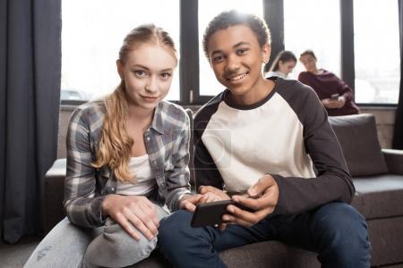 Teenage couple using smartphone