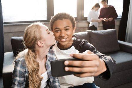 Teenage couple taking selfie