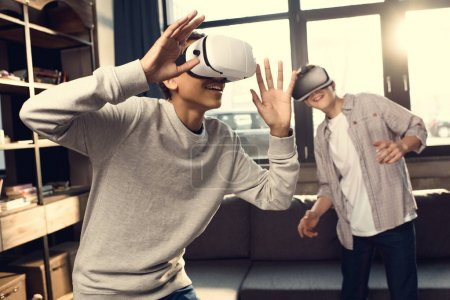 Photo for Teenage boys wearing virtual reality headsets at home, teenagers playing video games concept - Royalty Free Image
