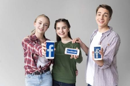 Photo for Smiling teenage friends showing smartphones with facebook logo isolated on grey - Royalty Free Image