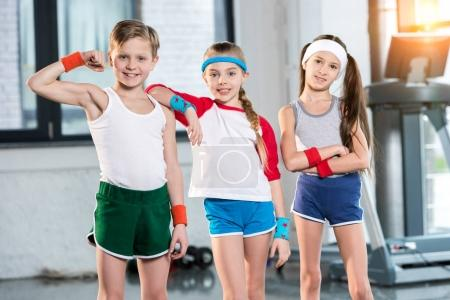 kids in sportswear posing at fitness studio