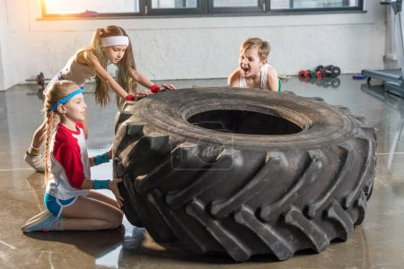 Photo for Adorable kids in sportswear training with tire at fitness studio, children sport concept - Royalty Free Image