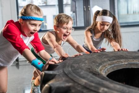 kids training with tire at fitness studio