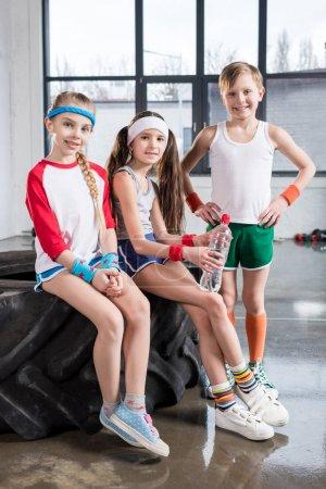 kids sitting on tire at fitness studio