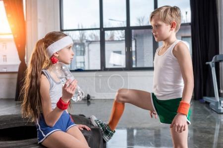 little boy and girl in sportswear talking
