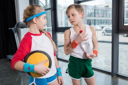 little boy and girl in sportswear talking