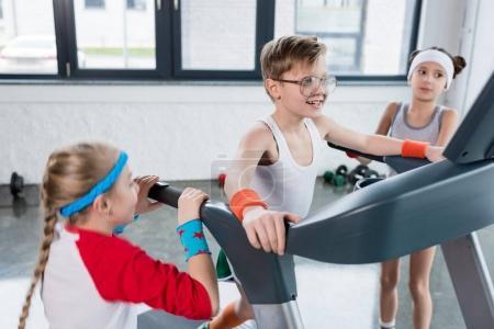 kids in sportswear training on treadmill