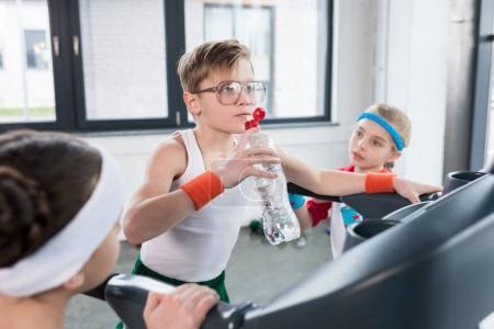 Foto de Niños graciosos en la formación deportiva en la caminadora en el gimnasio junto, niños deporte concepto - Imagen libre de derechos