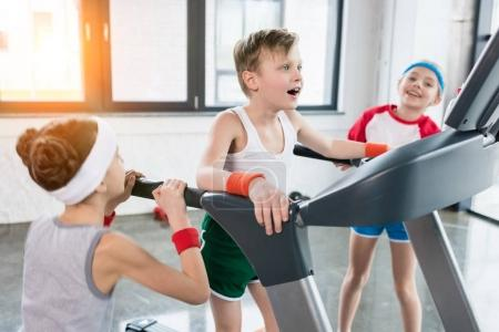 Photo for Funny kids in sportswear training on treadmill at gym together, children sport concept - Royalty Free Image