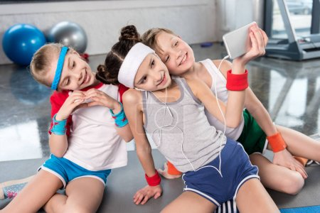 Photo for Cute smiling kids taking selfie with smartphone in gym, children sport school concept - Royalty Free Image