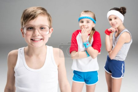 Photo for Portrait of smiling boy in glasses with girls behind isolated on grey - Royalty Free Image