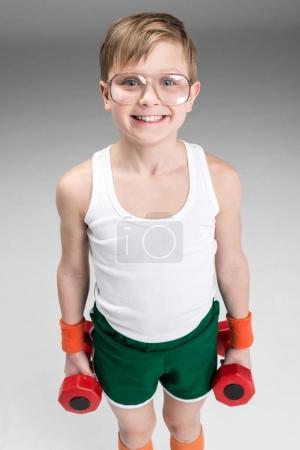 Photo for Portrait of smiling boy holding dumbbells isolated on grey - Royalty Free Image