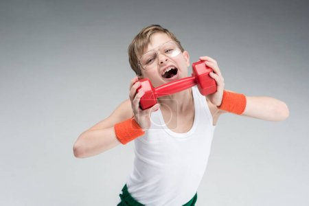 Photo for Portrait of excited boy holding dumbbell isolated on grey - Royalty Free Image
