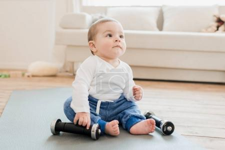 Baby boy playing with dumbbells