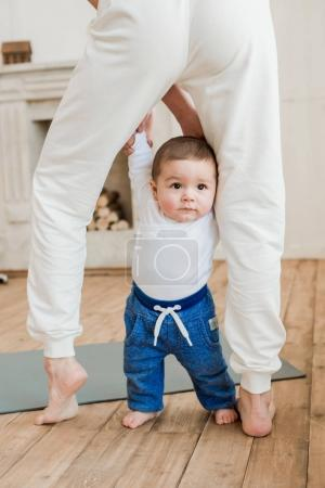 Photo for Cropped shot of adorable baby boy standing between mother's legs - Royalty Free Image