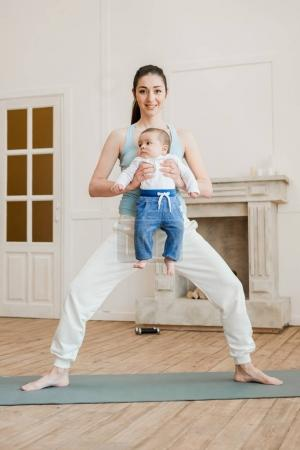 Photo for Mother with her child standing in yoga position on yoga mat at home - Royalty Free Image