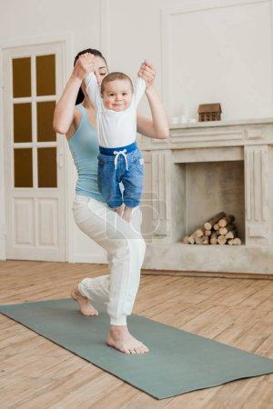 Photo pour Mère avec bébé garçon pratiquant le yoga sur tapis de yoga à la maison - image libre de droit
