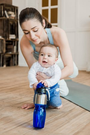 Photo for Woman in casual clothes relaxing with her son after fitness workout. Boy playing with water bottle - Royalty Free Image