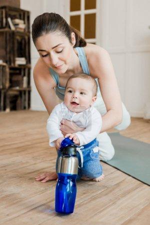 Photo pour Femme en vêtements décontractés se détendre avec son fils après l'entraînement de remise en forme. Garçon jouer avec bouteille d'eau - image libre de droit