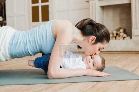 Photo for Side view of woman doing plank exercise and kissing her son - Royalty Free Image