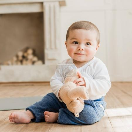 Photo for Smiling baby boy sitting with teddy bear toy on the floor - Royalty Free Image