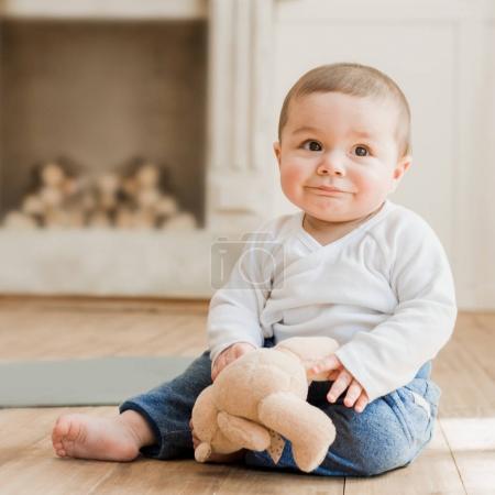 Photo pour Bébé garçon souriant assis avec un jouet ours en peluche sur le sol - image libre de droit