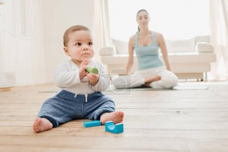 Photo for Baby boy playing with toys while his mother meditating at lotus position. - Royalty Free Image