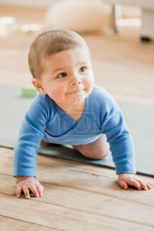 Baby boy crawling on yoga mat