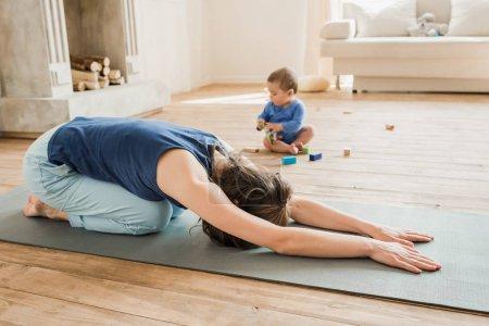 Photo pour Jeune femme avec bébé garçon pratiquant le yoga à la maison. Femme dans la position de l'enfant . - image libre de droit