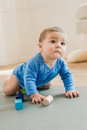 Foto de Adorable niño sentado en la estera de la yoga y jugar con los juguetes en casa - Imagen libre de derechos